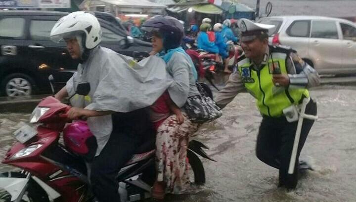 Di Tengah Hujan dan Genangan Air, Aiptu Udi Dorong Motor Pengendara yang Mogok